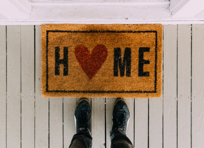 Home door mat with shoes in front of it